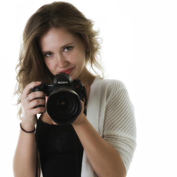 Fotografie: Jonge vrouw met een fotocamera in de hand.