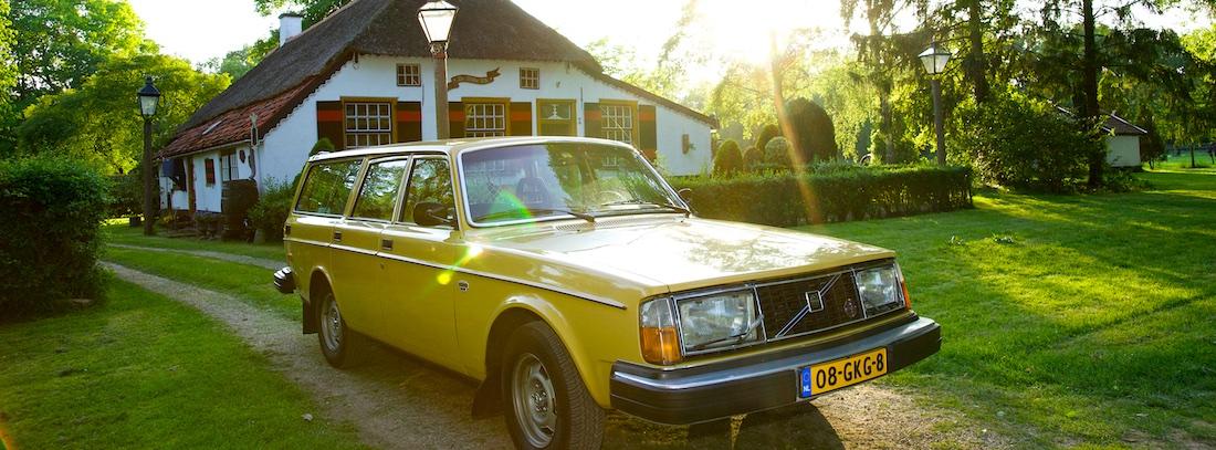 Volvo 245 GL voor boerderij met tegenlicht.